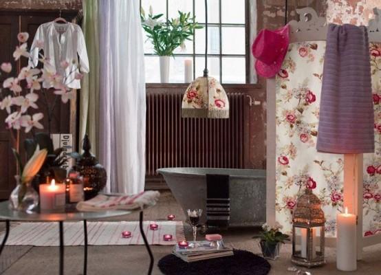 un bagno eclettico con candele, una vasca in metallo, una lampada floreale e un paravento coordinato