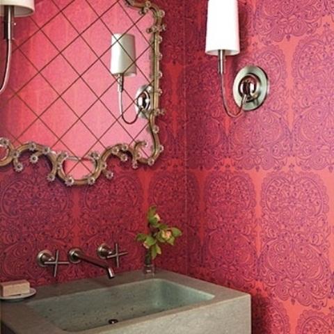 uno spazio fantasia rosa e viola brillante con un lavandino in cemento e uno splendido specchio decorato