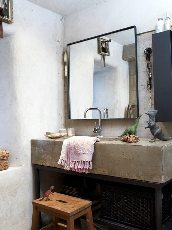 un bagno wabi-sabi con un lavandino in cemento, un grande specchio, uno sgabello di legno, asciugamani luminosi e dinosauri