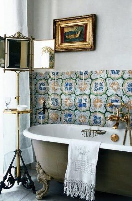 un bagno chic con piastrelle marocchine luminose, una vasca grene con piedini, opere d'arte e un fantastico specchio su un supporto