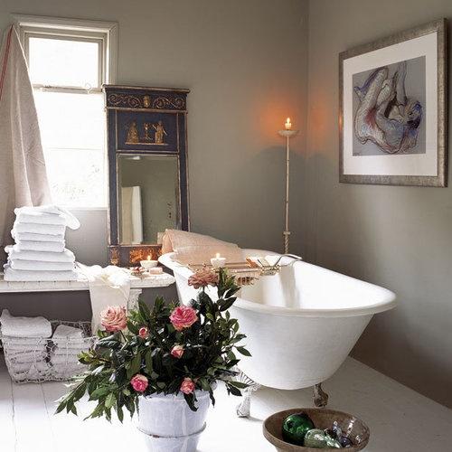 un bagno pulito con pareti grigie, un'elegante vasca con piedini, asciugamani bianchi e uno splendido specchio in una cornice unica