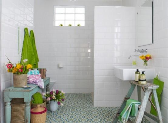 un bagno neutro con un luminoso pavimento di piastrelle a mosaico, mobili in legno shabby chic in colori pastello e fiori in vaso