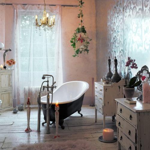 un romantico bagno vintage e shabby chic con comò shabby, una vasca vintage con piedini, candele, una gabbia e un lampadario di cristallo