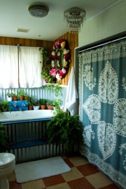 un bagno boho rilassato con una coperta boho sul muro, una vasca rivestita di metallo, vegetazione in vaso e fiori e piastrelle a quadri