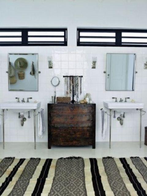 un bagno monocromatico con un tappeto a righe, un comò macchiato di scuro e cappelli di paglia