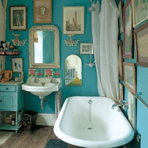 un bagno vintage con un muro a galleria boho, una vasca con i piedini, un lavandino a muro e una console chic