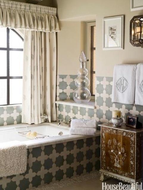 un bagno neutro di ispirazione marocchina con piastrelle marocchine, un lavabo in legno intarsiato e tende stampate