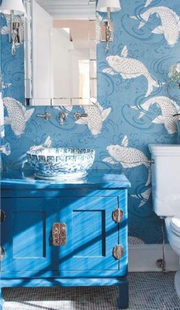 un bagno blu con carta da parati con stampa di pesci, un lavabo blu brillante, un lavandino dipinto e uno specchio chic