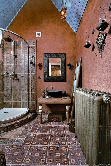 un boho incontra un bagno vintage con pareti in gesso rosso, piastrelle marocchine scure sul pavimento e nella doccia, lanterne a candela e uno specchio decorato