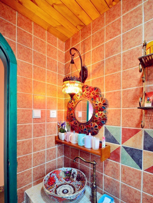 un bagno colorato con piastrelle ocra, luminose geometriche, uno specchio in mosaico e un lavabo a vaso dipinto a mano