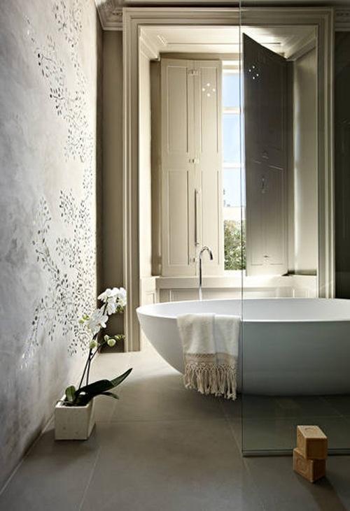 un bagno neutro con pareti in gesso, una grande vasca e saponi fatti a mano direttamente sul pavimento