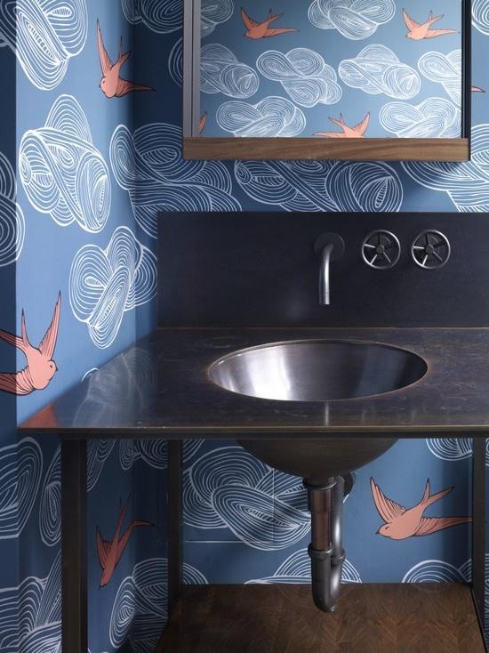 un bagno fatto con carta da parati blu e uccelli corallo, un mobile da toeletta macchiato e un lavandino di metallo scuro