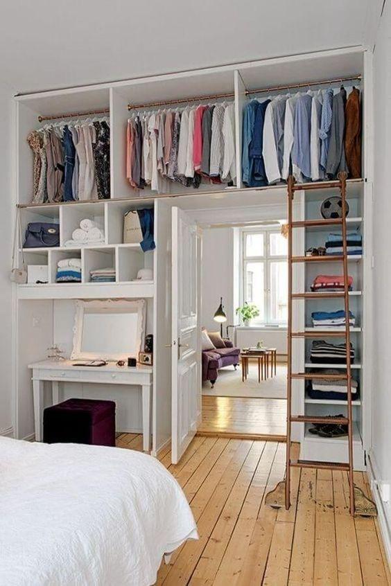 un intero armadio aperto con molti ripiani è integrato sopra la porta e su entrambi i lati per risparmiare più spazio possibile