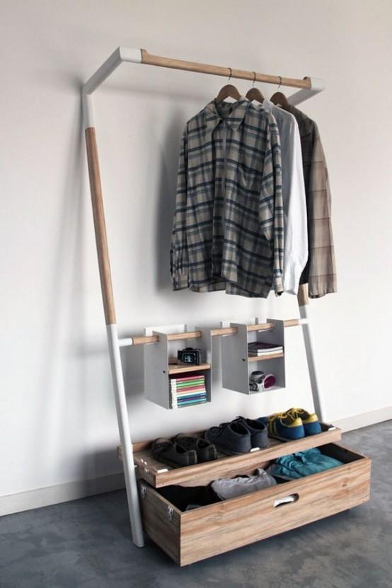 un armadio aperto piccolo ed elegantemente organizzato con un cassetto per i vestiti, alcuni appendiabiti e soem contenitori aperti sospesi per gli accessori