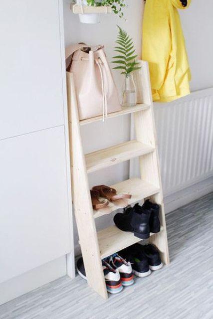 una piccola scala in legno usata come ripiano per scarpe e borse è un'idea semplice per una camera da letto o un ingresso