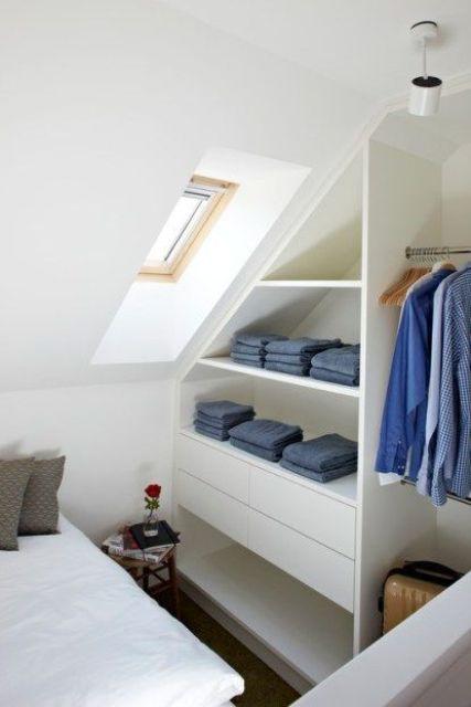 un elegante ripostiglio per abiti da soffitta con ripiani e cassetti aperti è un'idea elegante e confortevole per una piccola camera da letto