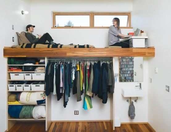un armadio aperto con appendiabiti, scatole e scaffali aperti e una piattaforma con un ufficio in casa e un divano letto in cima