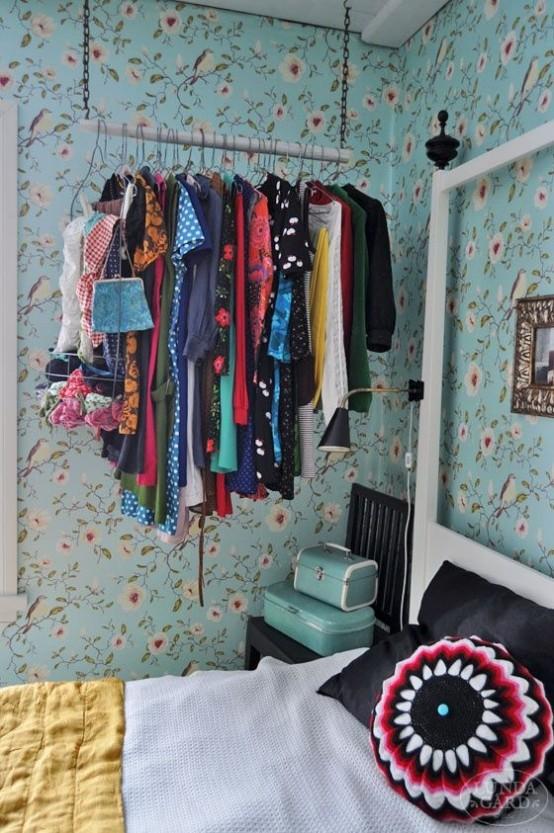 un armadio con catena e bastone di legno con appendiabiti è un'idea non ingombrante e ariosa che rende i vestiti parte dell'arredamento
