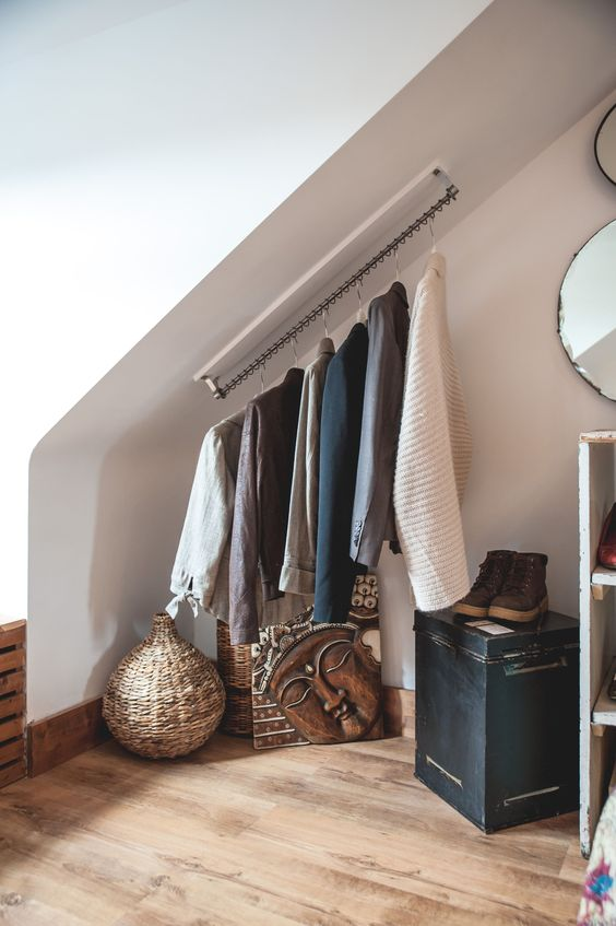 una mansarda con un supporto per appendiabiti attaccato direttamente al soffitto è un ottimo modo per risparmiare spazio