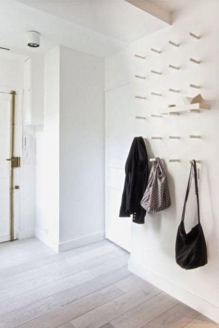 un muro bianco con molti ganci morbidi per appendere vestiti e borse o persino posizionare mensole e riporre scarpe su di loro