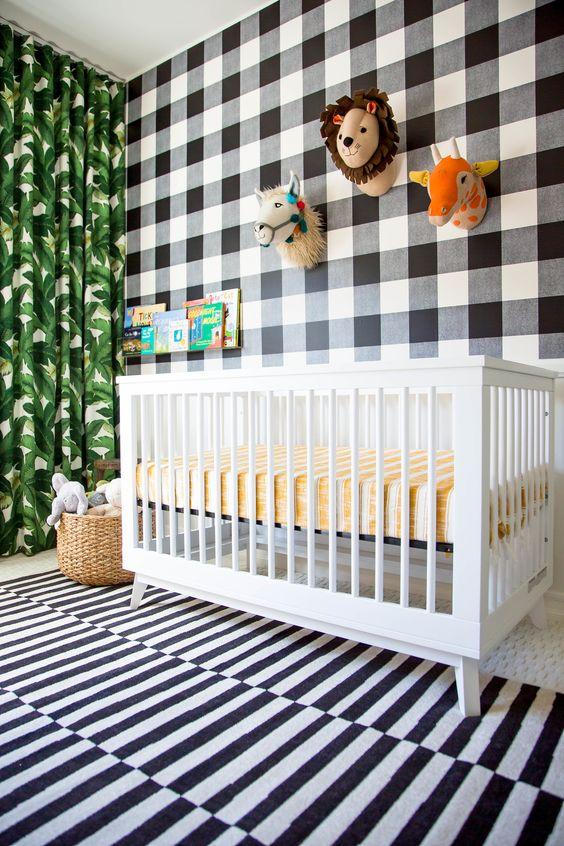 un divertente cameretta tropicale con un mix di stampe: un muro a quadri scozzese, un tappeto a righe e una tenda con stampa di foglie tropicali