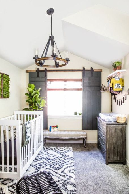 un accogliente cameretta rustico con una ghirlanda di nappe, tappeti stampati, un pouf in legno e molto verde