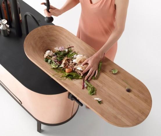 un'isola da cucina curva ed elegante con un piano di lavoro nero e un tagliere aggiuntivo sulla parte superiore è una splendida opzione per uno spazio minimalista