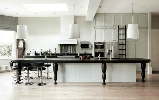 un'isola cucina bianca ricoperta da un grande tavolo nero per allungarla e renderla più funzionale