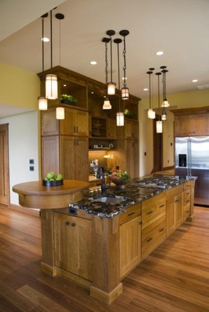 un'isola da cucina rustica di grandi dimensioni con molto spazio di archiviazione, un piano di lavoro in pietra e una tavola di legno rotonda per il taglio o la visualizzazione
