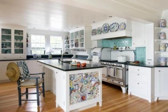 una solita isola cucina in bianco e nero è resa unica con mosaici colorati sul lato