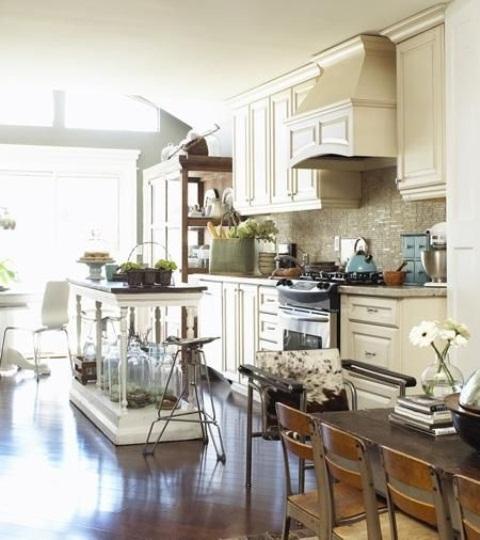 un'isola da cucina bianca vintage con gambe intagliate e un piano di lavoro scuro sembra molto leggera ed elegante
