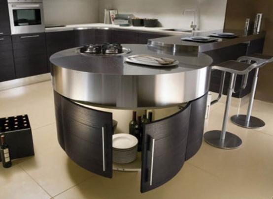un'isola cucina rotonda in legno tinto scuro e metallo sulla parte superiore più un bancone aggiuntivo che può servire un bancone per la colazione o un drink