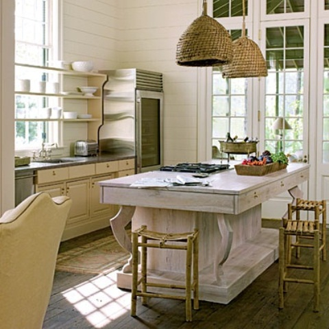 una grande isola da cucina in legno sbiancato si distingue per il suo colore e le sue finiture e aggiunge un'atmosfera rilassata allo spazio