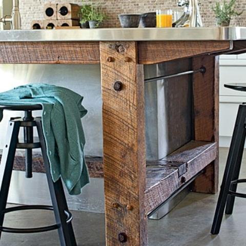 un'isola da cucina industriale in legno grezzo e un ripiano in metallo presenta uno spazio di archiviazione all'interno