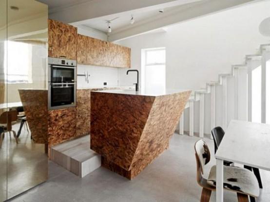 un'isola da cucina scultorea geometrica in compensato con spazio di archiviazione nascosto si distingue per la sua forma e le sue linee sorprendenti