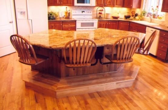 un'isola da cucina geometrica con un piano di lavoro in pietra e sedie attaccate proprio per risparmiare spazio
