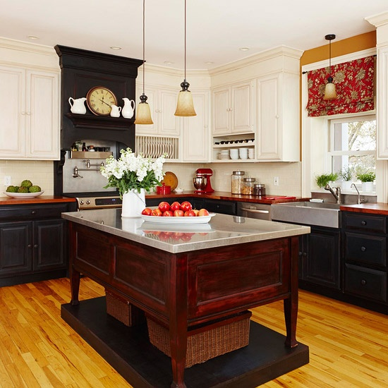 un'isola da cucina in legno di sequoia su una piattaforma con un piano di lavoro in metallo si distingue in una cucina nera e presenta uno spazio di archiviazione aperto