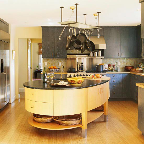 un'isola cucina asimmetrica con una parte curva, con tanti vani portaoggetti, un ripiano a giorno e un piano in pietra scura