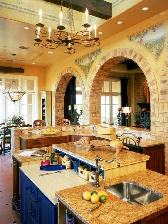 un'isola cucina creativa in tinta ricca con una credenza blu navy integrata all'interno con ripiani in pietra e un'ulteriore rialzata