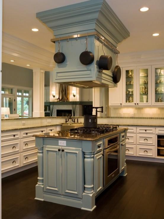 un'esclusiva isola cucina in due parti blu pallido con un piano di lavoro in legno tinto, un fornello integrato e alcune pentole sospese nella parte superiore