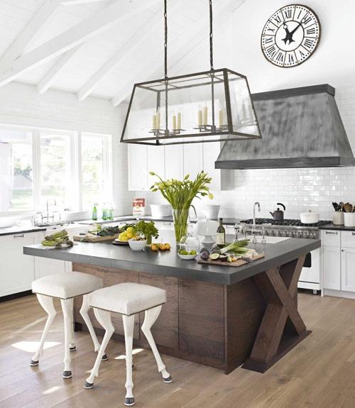 un'isola da cucina in legno tinto scuro con un piano di lavoro in legno fa una dichiarazione audace in una cucina bianca con un tocco vintage