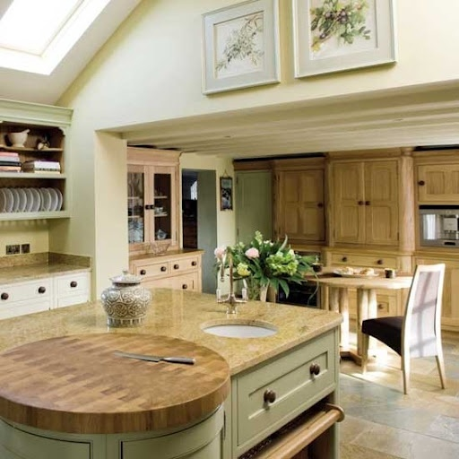 un'isola cucina vintage grigia con un controsoffitto butcherblock e un tagliere rotondo integrato proprio nella parte superiore