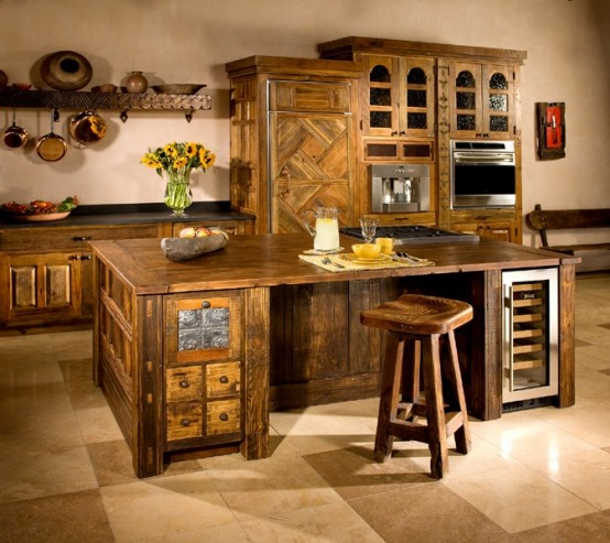 una grande isola da cucina in legno tinto scuro con cassetti e refrigeratori per bevande si abbina alla cucina e sembra molto accogliente