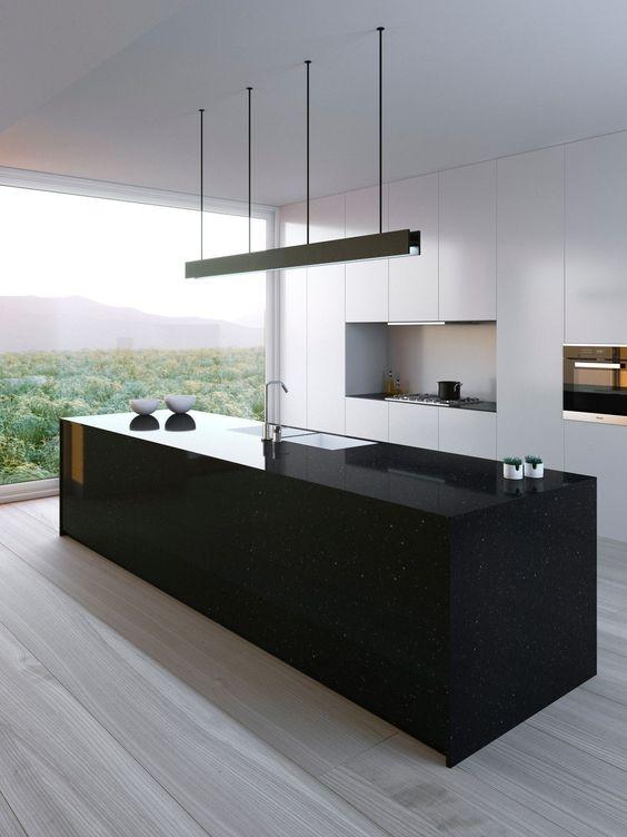 un'elegante isola da cucina nera sembra un monolite e contrasta con la cucina bianca e fa e afferma qui