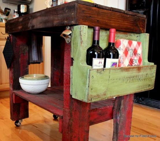 un'isola da cucina shabby chic macchiata di scuro e rossa su rotelle più una scatola di legno verde per la conservazione