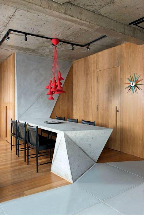 un'isola da cucina scultorea in cemento e un tavolo da pranzo che si estende fino al muro fanno una dichiarazione