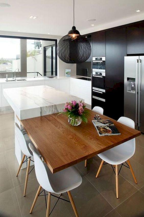 un'isola da cucina a contrasto in pietra bianca e un tavolo in compensato è un audace complemento alla cucina monocromatica