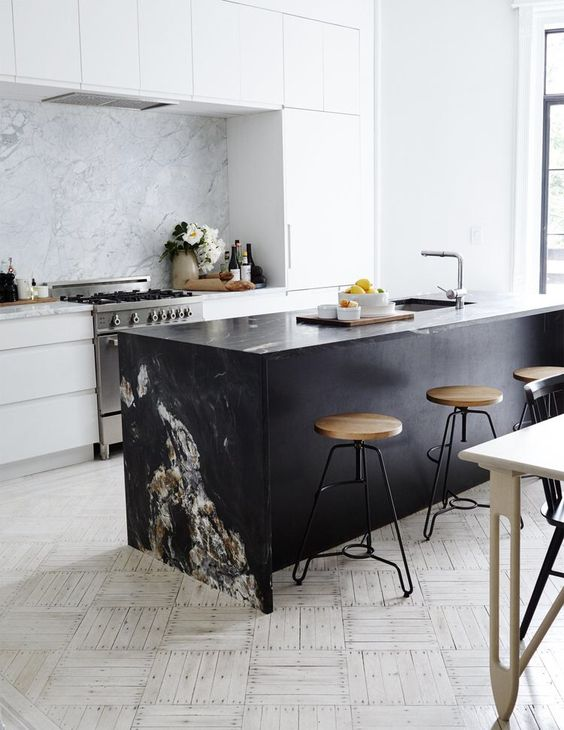 una moderna cucina bianca e un'isola da cucina nera, un paraschizzi in marmo e un piano di lavoro per legarli