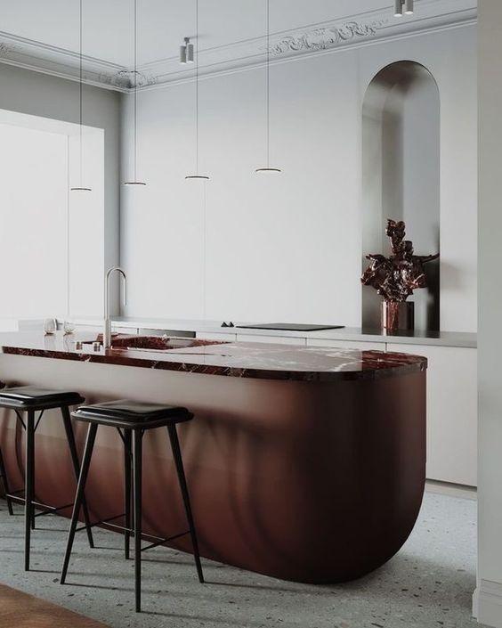 una splendida isola da cucina in metallo e pietra in ricchi toni ruggine è una dichiarazione fantastica con colore e forma per una cucina neutra