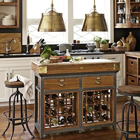 una piccola isola da cucina in metallo e legno con cassetti e portabottiglie all'interno è un pezzo molto salvaspazio